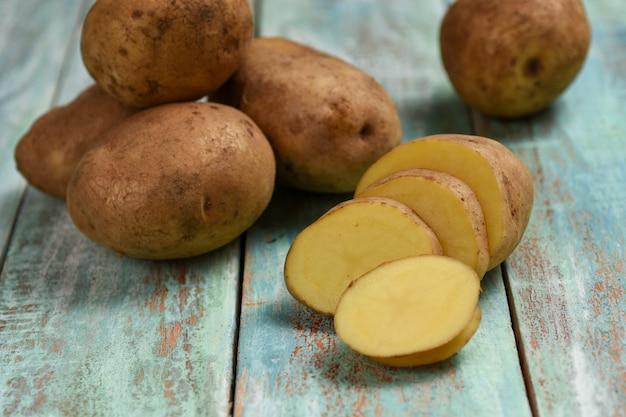 生のジャガイモ木製の背景に古い袋の新鮮なジャガイモ