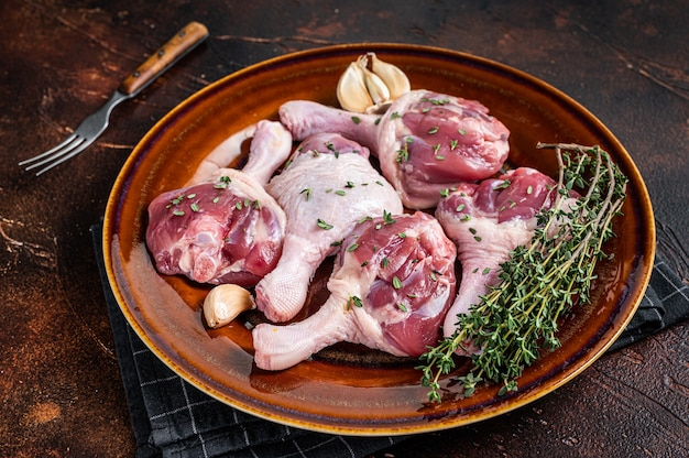 Сырое мясо птицы - голени утиных ножек на деревенской тарелке с зеленью. темный фон. вид сверху.
