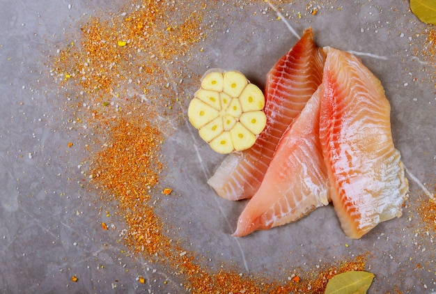 Raw preparation fish fillets tilapia on cutting granite cooker of board