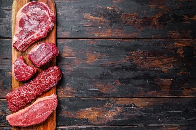 Raw prime black angus beef steaks fillet mignon, rib eye or cowboy, striploin or new york, skirt or machete. wooden dark background. top view. copy space.