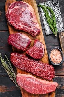 Raw prime black angus beef steaks fillet mignon, rib eye or cowboy, striploin or new york, skirt or machete