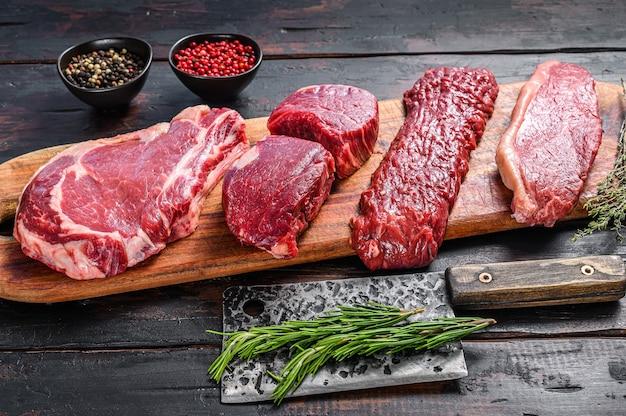 Raw prime black angus beef steaks fillet mignon, rib eye or cowboy, striploin or new york, skirt or machete.