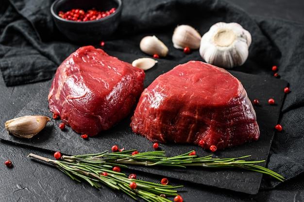 Raw prime black angus tenderloin beef steaks. black background. top view