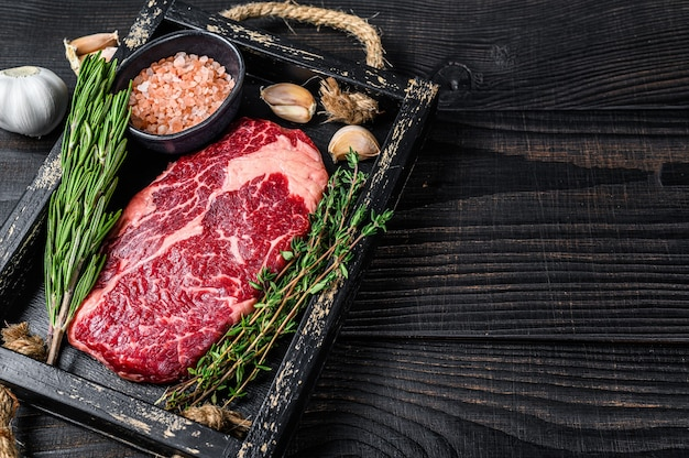 Raw prime rib eye beef meat steak in a butcher wooden tray with herbs.