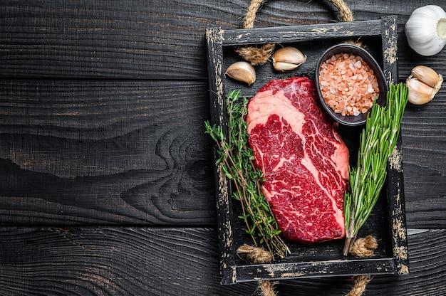 木製のテーブルにハーブを添えた肉屋の木製トレイに生のプライムリブアイビーフミートステーキ。上面図。