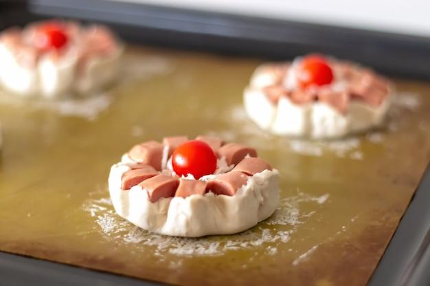 Мини-пирог из сырого слоеного теста с колбасой и помидорами черри, готовый к выпечке. выборочный фокус.
