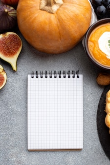 Raw pumpkin and empty notebook