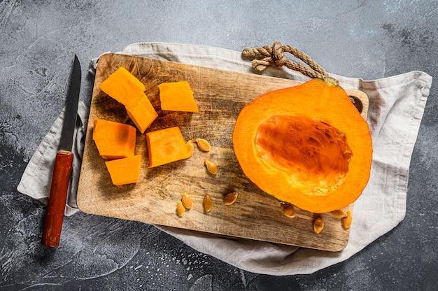 カッティングボードに生のカボチャを立方体にカットします。灰色の背景。美味しくてヘルシーな料理。かぼちゃの種。ビーガンフード