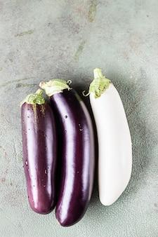 Сырые фиолетовые и белые баклажаны, solanum melongena или баклажаны с каплями воды. скопируйте пространство.
