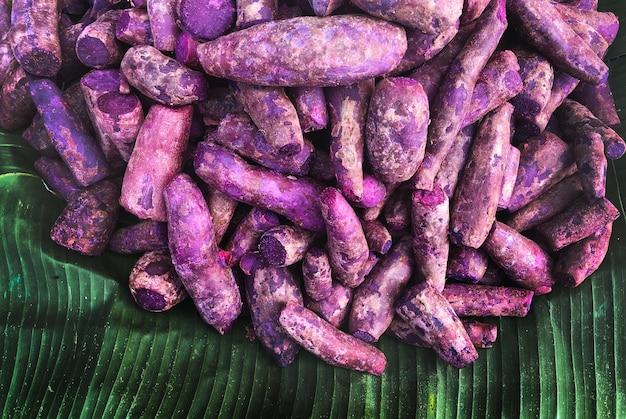 Сырой фиолетовый сладкий картофель на зеленом банановом листе свежий сладкий картофель сверху