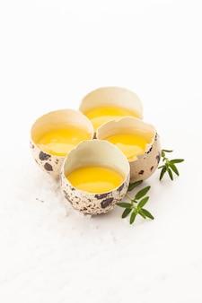 Сырые перепелиные яйца с желтком и зеленью на белом фоне