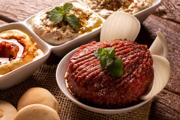 Сырая киса, украшенная мятой, хумусом, баба ганушем, луком и хлебом.