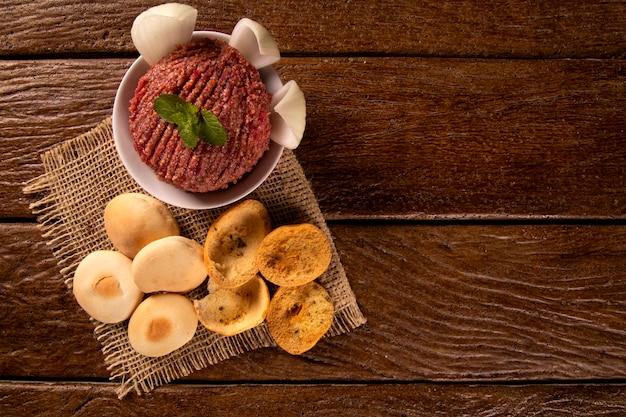 Сырая киса, украшенная мятой, помидорами, луком и листьями салата.