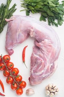 신선한 야채, 허브, 향신료 세트를 곁들인 생 토끼 고기, 흰 돌 배경, 평면도