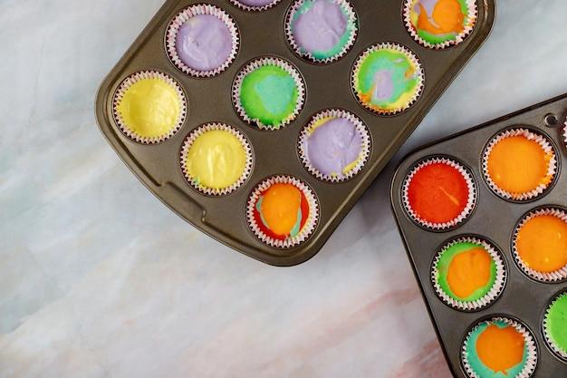 2つのオーブントレイに生のレインボーカップケーキ。上面図。
