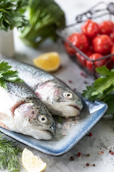 Raw rainbow trout fish on a plate, greens and fresh vegetables for preparing healthy and tasty food. healthy diet and delicious culinary concept.