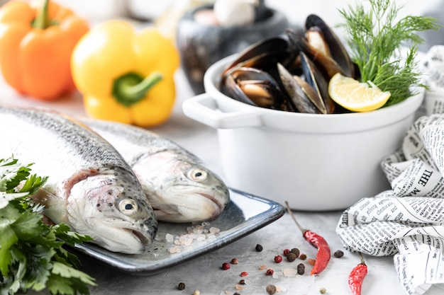Raw rainbow trout fish on a plate, greens and fresh vegetables for preparing healthy and tasty food. white pan with mussels on a concrete