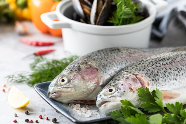 Raw rainbow trout fish on a plate, greens and fresh vegetables for preparing healthy and tasty food.