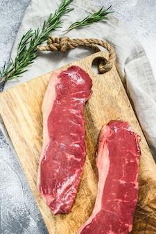 Raw ramp steak, fresh meat, marbled beef. dark wall. flat lay