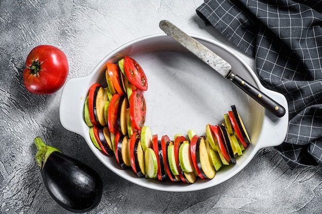 Raw ratatouille, traditional french vegetable dish. gray background. top view.