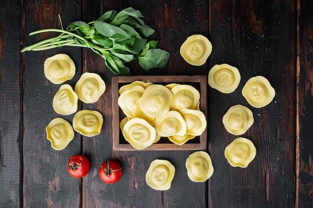 바질과 토마토 세트, 나무 상자, 오래 된 어두운 나무 테이블에 원시 라비올리, 평면도 평면 누워