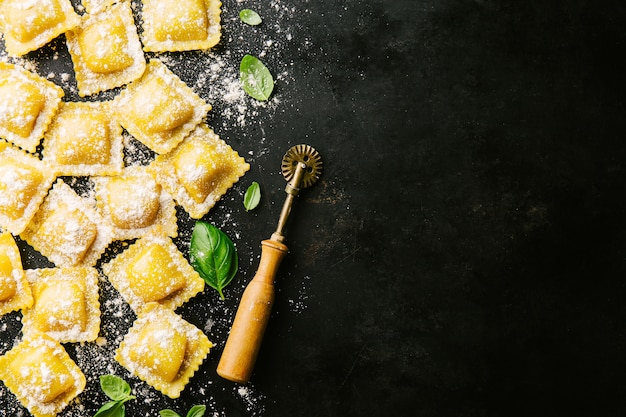 Raw ravioli with basil and flour on dark