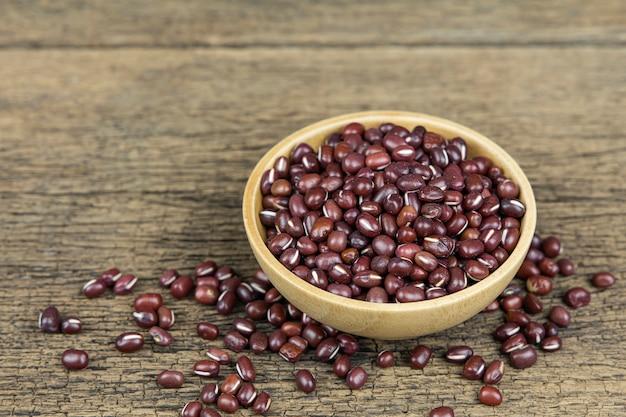 木製のテーブル背景に木製のボウルに生の小豆の種子。