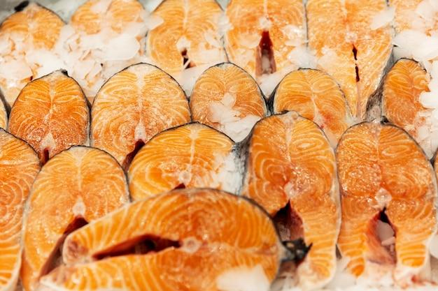 Сырые стейки из красной рыбы на льду на прилавке в магазине. крупный план. здоровое питание и витамины. вертикальный.
