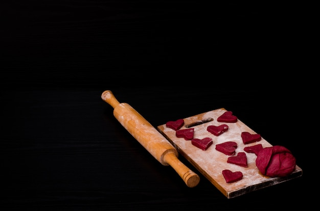 Raw red heart-shaped cookies and dough on wooden board with flour, wooden rolling pin. black . preparing for valentine's day