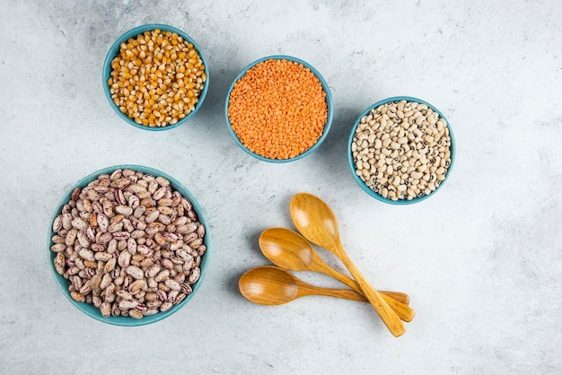 生の赤レンズ豆、トウモロコシ、豆を青いボウルに入れ、木のスプーンで。