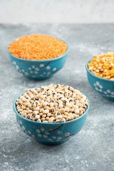 青いボウルに生の赤レンズ豆、トウモロコシ、白豆。