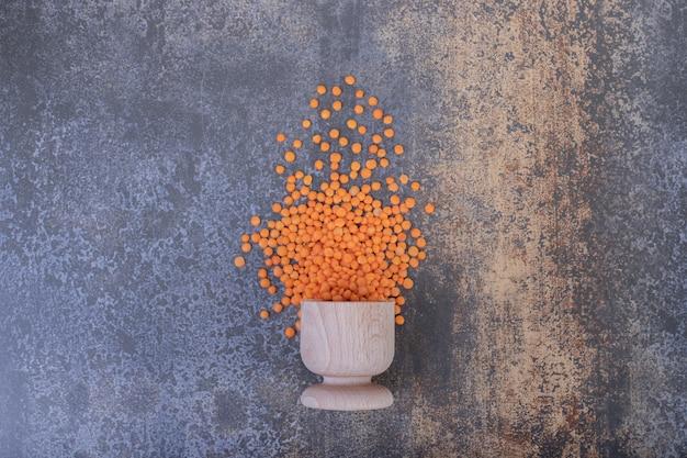 青の背景に木製のボウルに生の赤レンズ豆。