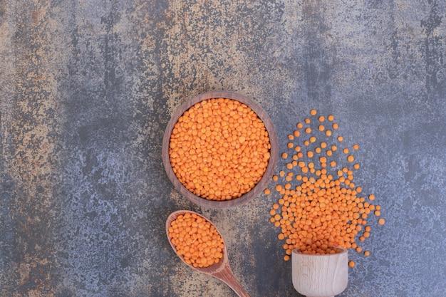 青の木製ボウルに生の赤レンズ豆。