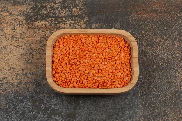 木の板に生の赤レンズ豆。