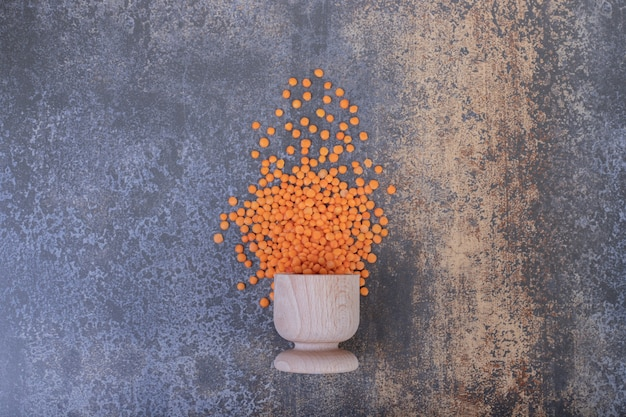 Raw red lentils in wooden bowl on blue background.