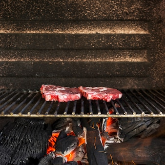 Raw red meat on grill pit with hot charcoal briquettes