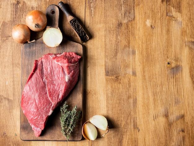 커팅 보드에 향신료와 쇠고기의 원시 붉은 고기. 복사 공간이 있습니다.
