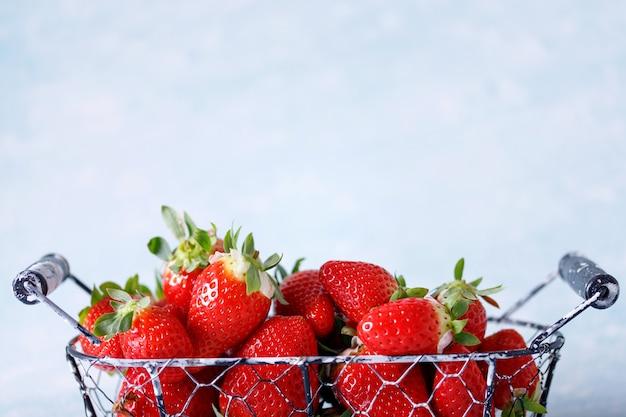 青の背景に束の生の赤い有機イチゴ。
