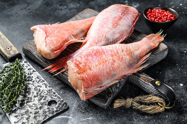 Raw red perch or seabass fish on a cutting board.   top view.