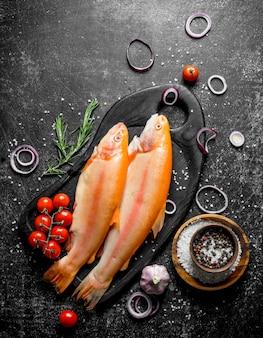 향신료, 토마토, 양파 링과 원시 붉은 송어.