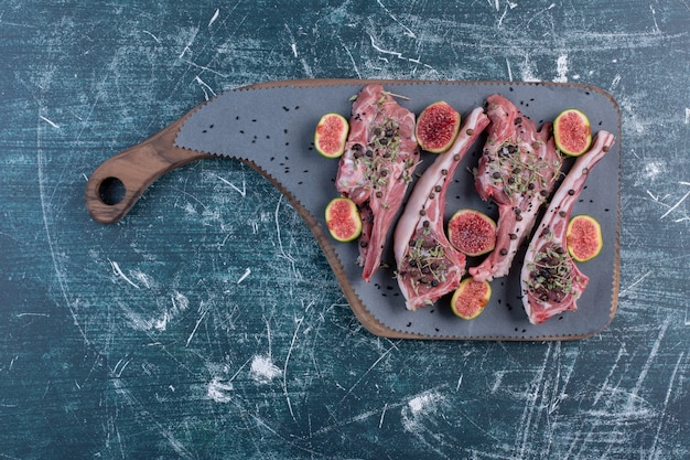 Raw rib chops in wooden board with figs and dried herbs.