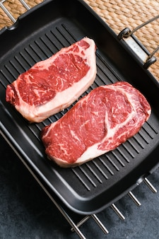 Сырой рибай и стриплойн из говядины new york на черной сковороде для гриля