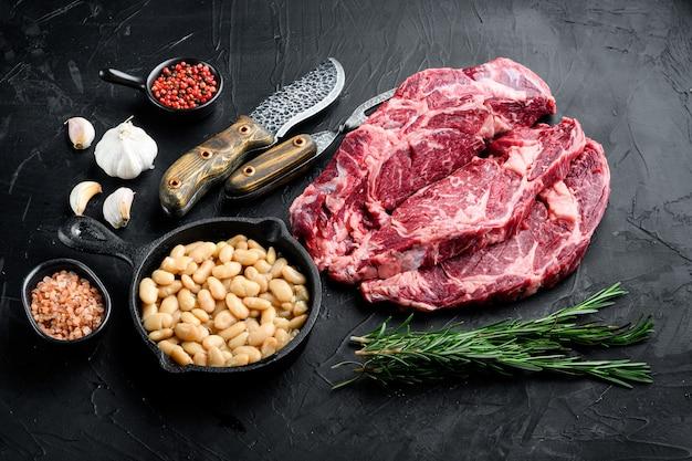 Стейк из мраморного мяса сырой говядины рибай с перцем и травами на черном фоне