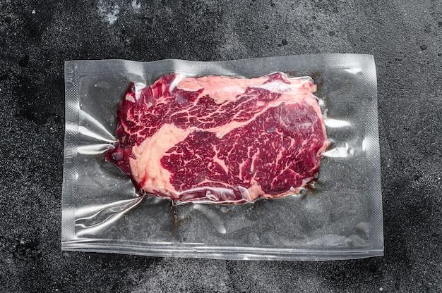 Сырой стейк из говядины рибай в вакуумной упаковке.