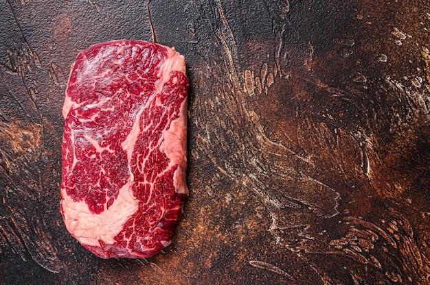 나무 테이블에 요리를 위해 준비 된 정육점 테이블에 원시 갈비뼈 쇠고기 고기 스테이크. 평면도.