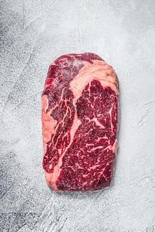 그릴을 위해 준비된 테이블에 원시 갈비뼈 쇠고기 고기 스테이크. 흰색 배경. 평면도.