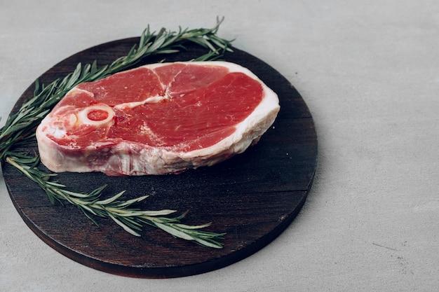 Raw rib-eye beef steak on wooden cutting board on gray background close up