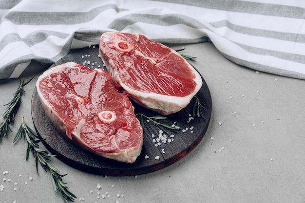 Raw rib-eye beef steak on wooden cutting board on gray background