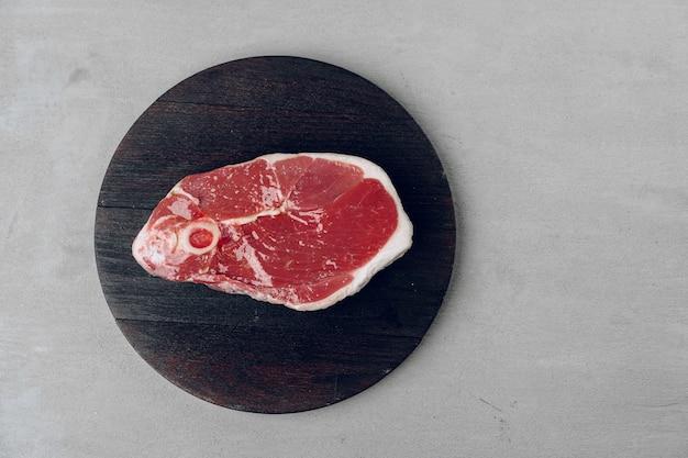 Raw rib-eye beef steak on wooden cutting board on gray close up