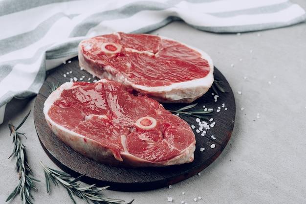 Raw rib-eye beef steak on wooden cutting board on gray
